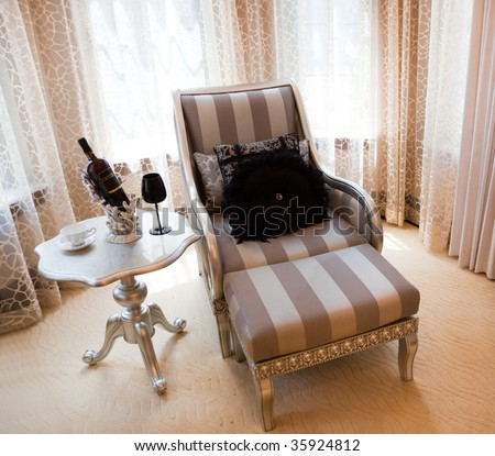 Reclining chair and table  by the window - stock photo