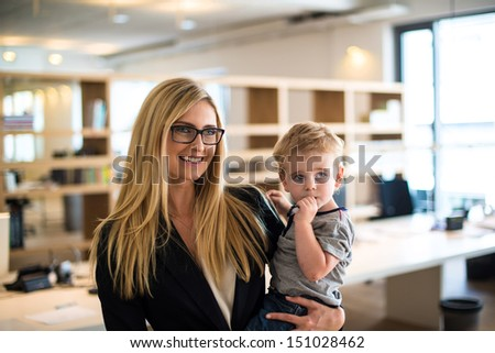 Reconciliation of family and work life: Attractive blond woman in business attire proudly carrying a small boy in her arm in office environment - stock photo