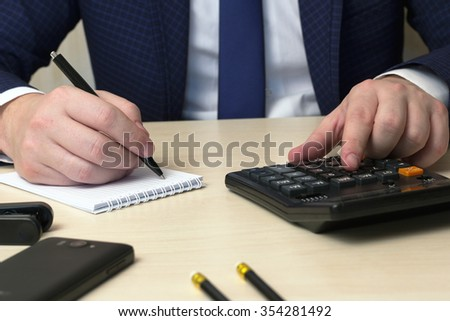 record by the handle of the business plan and calculation on the calculator at a table - stock photo