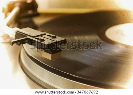 record player stylus on a rotating disc in sepia tone - stock photo