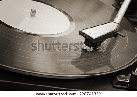 Record player stylus on a rotating disc, Picture of a vinyl record playing. Old Sepia film processed.