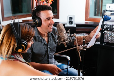 Record producer showing young singer the right way to perform the song - stock photo