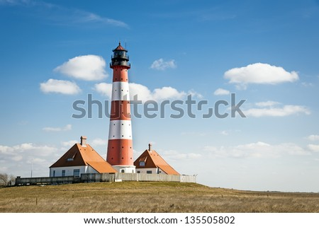 Recording in landscape from the lighthouse westerhever on a sunny day with blue sky and white clouds. - stock photo