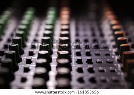 Recording studio audio mixing console looking across the control knobs - stock photo