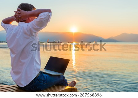 Recreational entrepreneur. Man with laptop in the morning on the beach working - stock photo