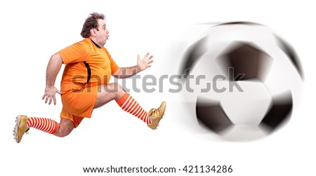 Recreational fat football player kicking the ball isolated on a white background.  Fat  man soccer player running with giant ball   - stock photo