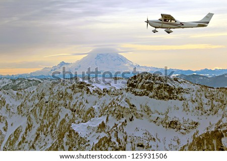 Recreational flying over picturesque snow covered mountains - stock photo
