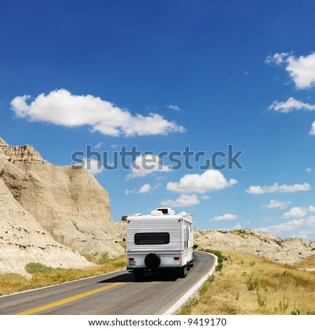 Recreational vehicle on scenic road in Badlands National Park, North Dakota. - stock photo