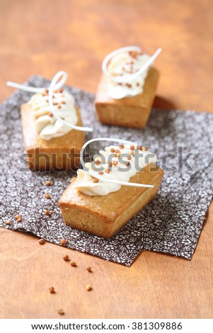 Rectangular Cakes with White Chocolate Cream Cheese Frosting decorated with caramelized walnuts, on a wooden table. - stock photo