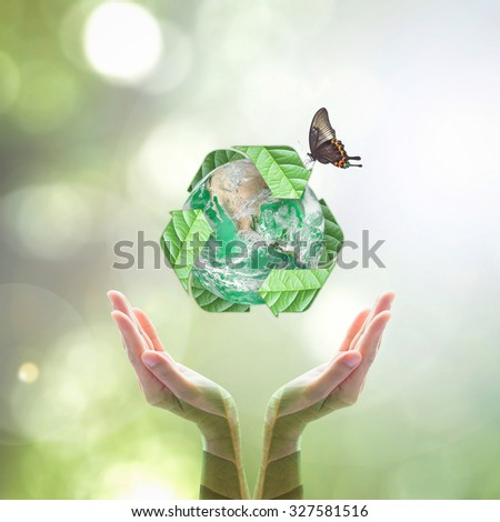 Recycle arrow sign leaves around green globe with butterfly over woman human hands on blurred abstract bokeh background: Recycle, reduce, reuse idea concept: Elements of this image furnished by NASA