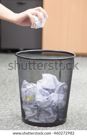 Recycle bin filled with crumpled papers - stock photo