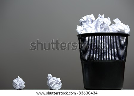 Recycle bin filled with crumpled papers. Gray background, - stock photo