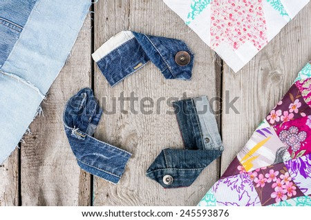 Recycle Logo from used old denim fabric on old grey wooden background - stock photo