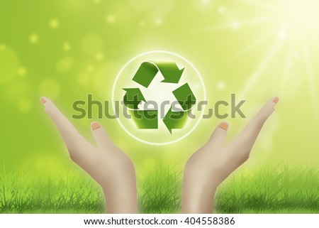 Recycle sign in hands against green spring background. Earth day concept