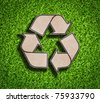 Recycle sign on green grass background - stock photo