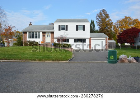 Recycle symbol on green trash container bagged leaves at curb of suburban high ranch style home residential neighborhood fall season blue sky clouds USA - stock photo