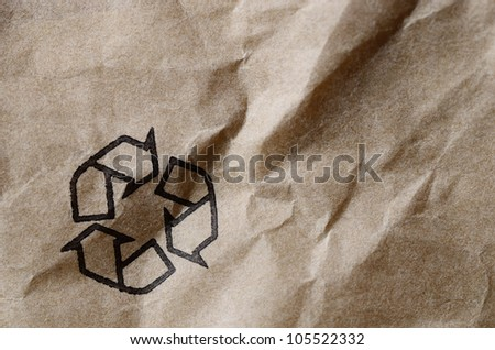 recycle symbol printed on brown recycled paper - stock photo
