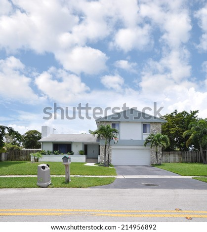 Recycle Trash container on front yard lawn of Suburban Back Split style home residential neighborhood USA blue sky clouds