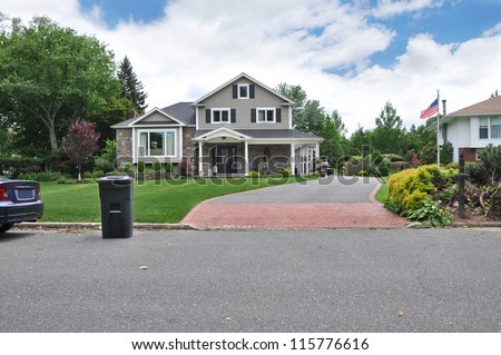 Recycle Trash Container on street curb of Large Cape Cod Style Suburban Neighborhood Home with brick and blacktop driveway - stock photo