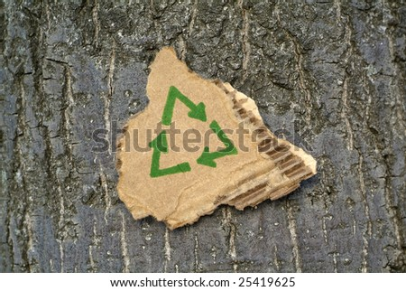 Recycled cardboard surrounded by tree bark. - stock photo