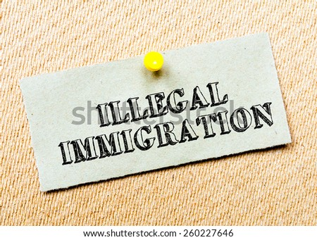 Recycled paper note pinned on cork board. Illegal Immigration Message. Concept Image - stock photo