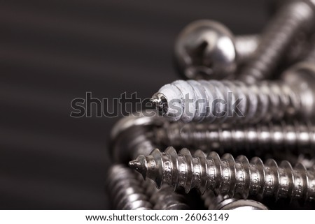 Recycled screws with one showing signs of previous use. Shot with copy space on black to the left of the frame. Drywall dust caked to the threads of a panhead screw in a pile for use again.