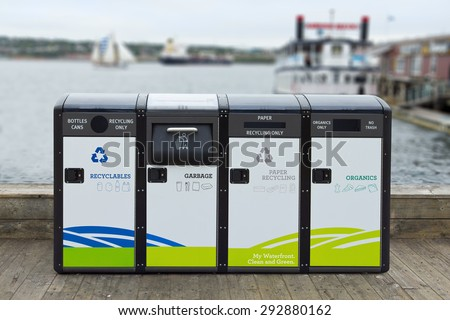 Recycling and garbage bins found on a waterfront pier with shallow depth of field