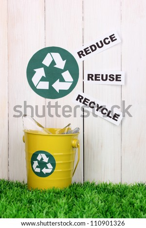 Recycling bin on green grass near wooden fence