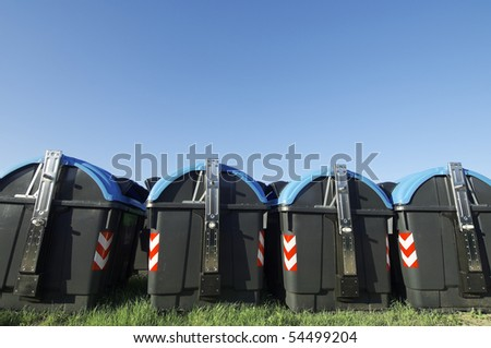 recycling bins for paper and glass with blue sky - stock photo