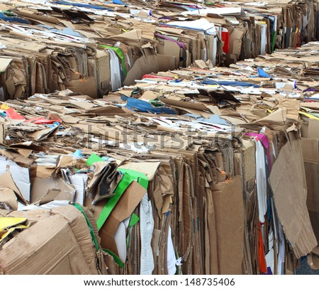 Recycling cardboard packaging concept with stacks of compressed corrugated paper garbage as a symbol to recycle for conservation and the environmental technology business. - stock photo