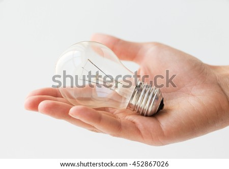 recycling, electricity, environment and ecology concept - close up of hand holding lightbulb or incandescent lamp - stock photo