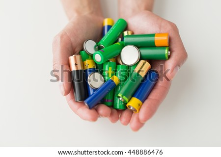 recycling, energy, power, environment and ecology concept - close up of hands holding alkaline batteries heap - stock photo