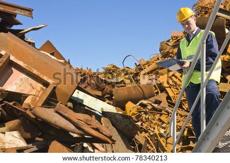 Recycling expert, standing on a metal staircase in front of a steel scrap heap - stock photo