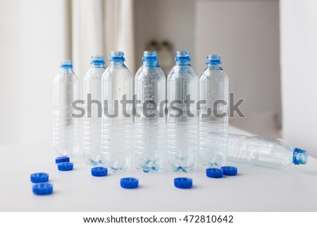 recycling, healthy eating and food storage concept - close up of empty used water bottles and caps on table