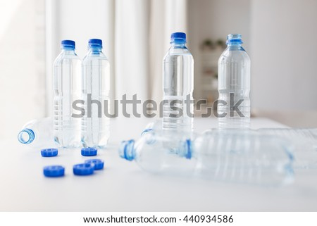 recycling, healthy eating and food storage concept - close up of plastic bottles with pure drinking water on table - stock photo