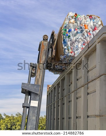 Recycling plastic bottles. Industrial machine crane with stack of empty crushed plastic drinking containers in cardboard box and large metal dumpster. Green bushes, blue sky and clouds background.  - stock photo