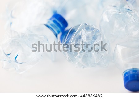 recycling, reuse, garbage disposal, environment and ecology concept - close up of empty used crashed plastic water bottles on table - stock photo