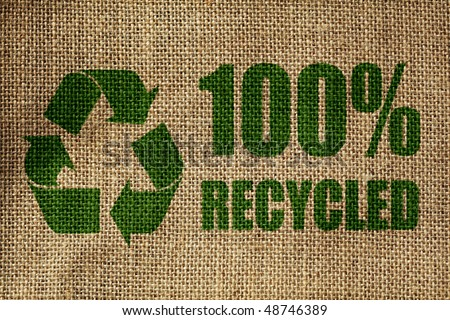 Recycling symbol and one hundred per cent recycled sign on the side of a hessian bag in green - stock photo