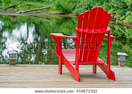 Red Adirondack chair at a lake - also known as a Muskoka chair in Canada, after the Ontario lake of the same name.  These chairs are an iconic symbol for successful retirement to a woodland cottage.