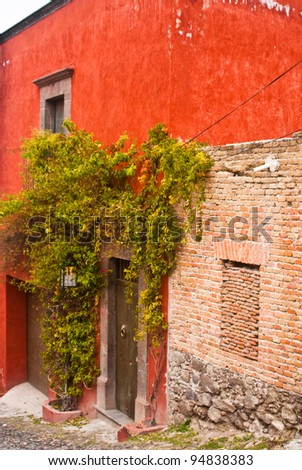 Red adobe house with brick walls in San Miguel de Allende, Mexico - stock photo