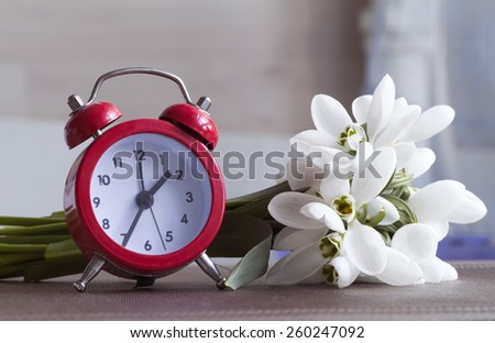 Red alarm clock and small bouquet of snowdrops. - stock photo