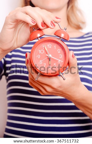 Red alarm clock in female hands - stock photo