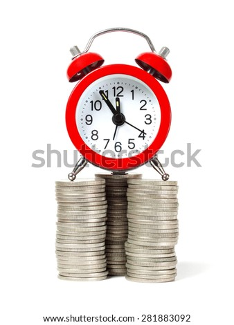 Red alarm clock on coin stacks isolated on white. - stock photo