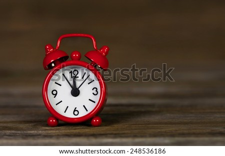 Red alarm clock on wooden old background: time five minutes to 12 o'clock. - stock photo