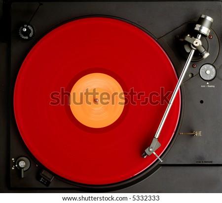 red album turning on black recordplayer - stock photo
