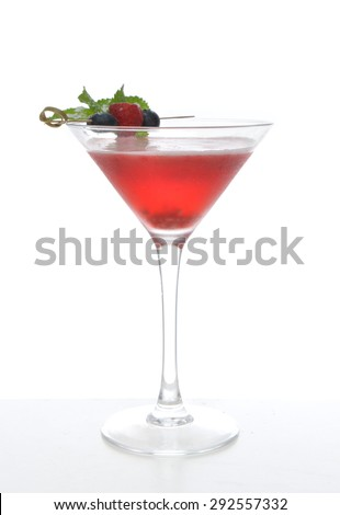 Red alcohol cosmopolitan cocktail decorated with mint blueberry and raspberry in martini cocktails glass on a white background - stock photo