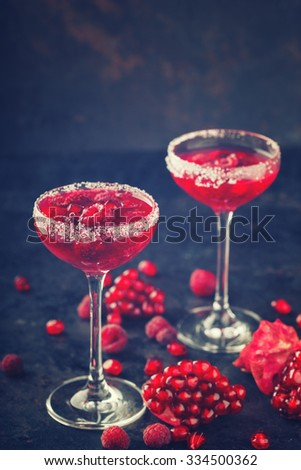 Red alcoholic cocktail with raspberry and pomegranate, in a glass glass on a black background.  Toned image. Vintage style.selective focus. - stock photo