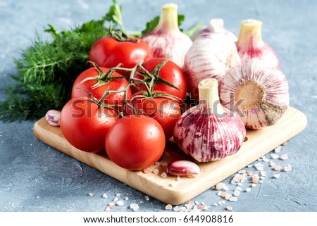 Red and beautiful tomatoes garlic bulbs on wooden board Parsley Dill Horizontal photo