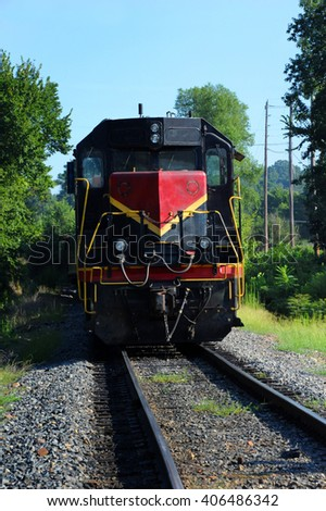 Red and black locomotive travels down railroad track in Arkansas.   - stock photo