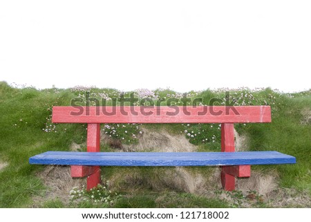 red and blue bench positioned at the edge on top of a cliff - stock photo